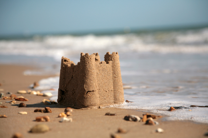 A sandcastle on the beach, with a wave approaching to wash it away
